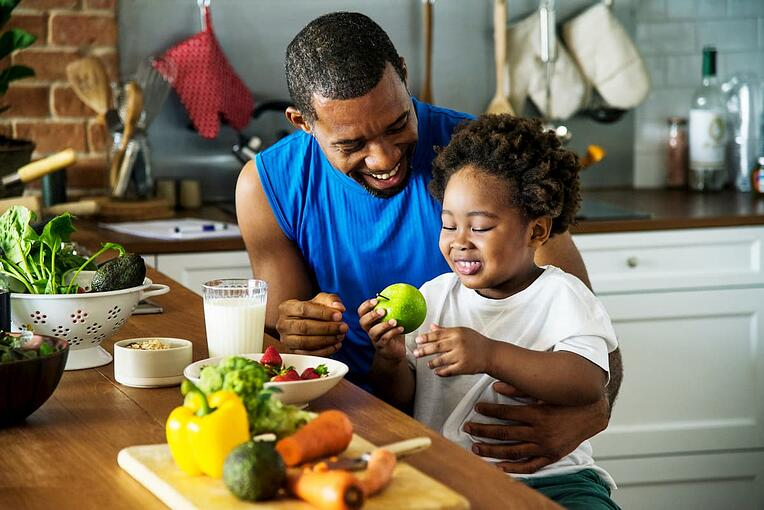 Father and son eating fruits and vegetables