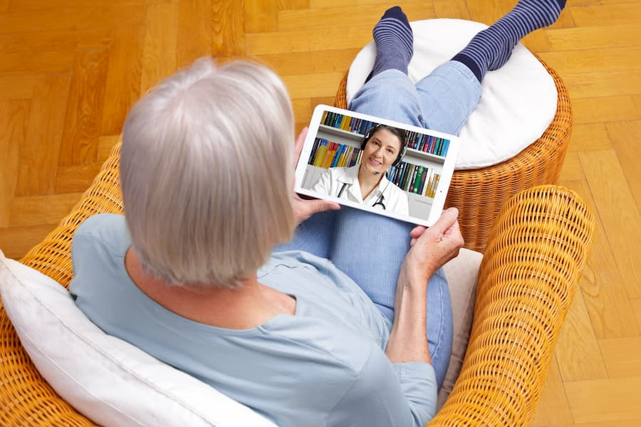 Senior talking to doctor during televisit on tablet