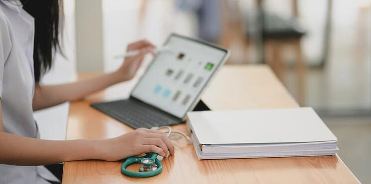Doctor looking over patient file on laptop