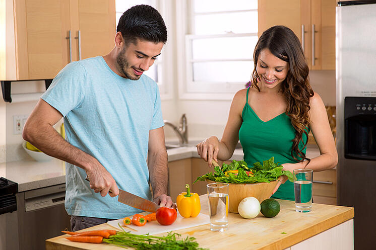 Couple preparing a salad in their kitchen